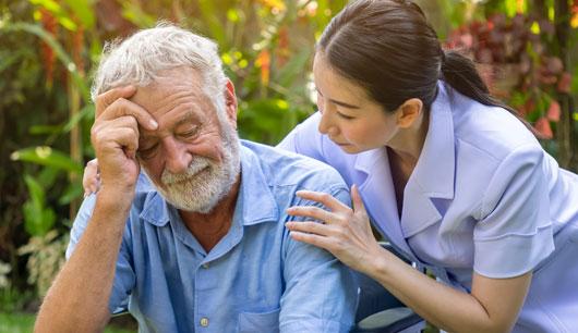 A female nurse assists an elderly patient.